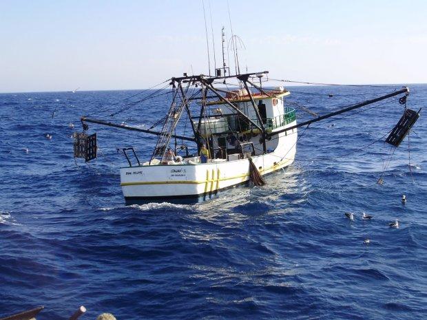 #Pracegover Foto: na imagem há um barco pesqueiro e o mar