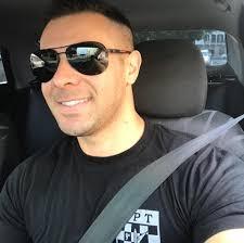 #Pracegover Foto: na imagem há um homem de óculos escuros em um carro e com cinto de segurança