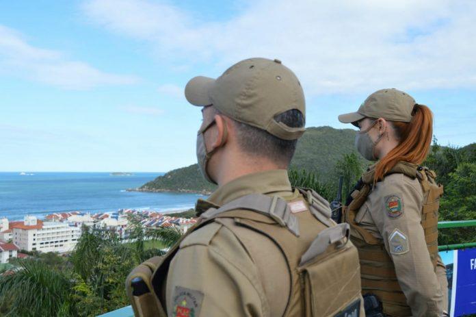 #Pracegover Foto: na imagem há dois policiais e o mar