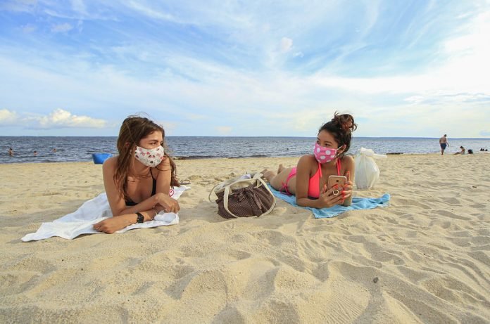#Pracegover Foto: na imagem há duas mulheres na faixa de areia e no fundo o mar