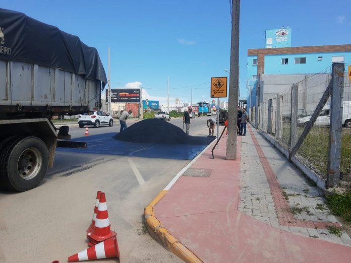 #Pracegover Foto: na imagem há um caminhão, carros, cones e homens em uma via