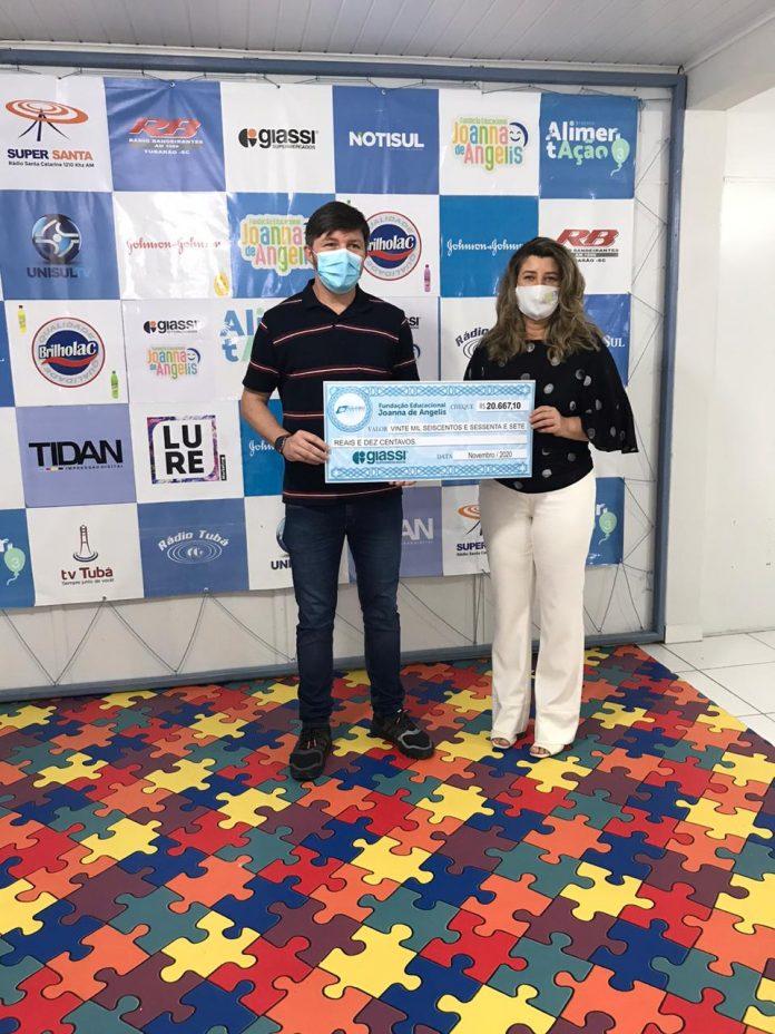 #Pracegover Foto: na imagem há duas pessoas, um homem e uma mulher. Ambos seguram um cheque simbólico