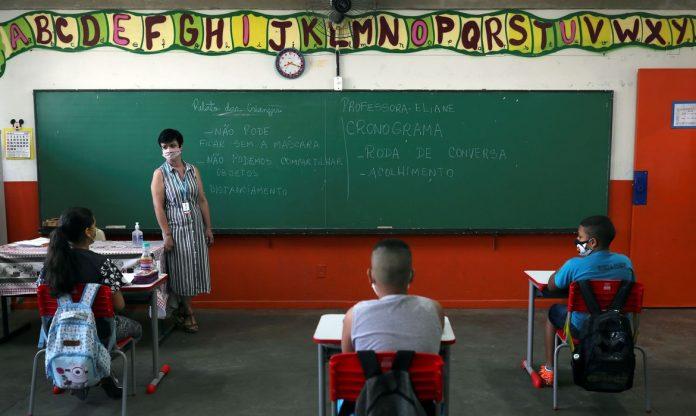 #Pracegover Foto: na imagem há uma mulher, algumas crianças e um quadro
