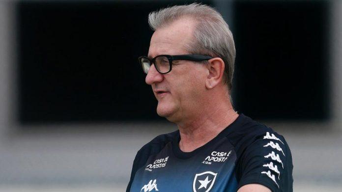 #Pracegover Foto: na imagem há um homem de cabelo grisalho, de óculos e com uniforme de treino do Botafogo, time de futebol