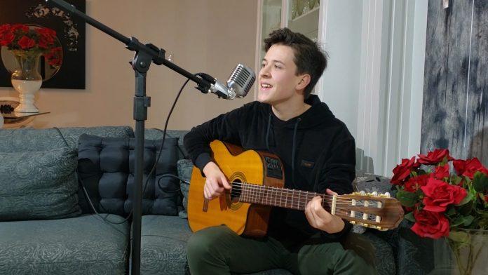 #Pracegover Foto: na imagem há um jovem com um violão, um sofá, um vaso de flores, microfone e um pedestal