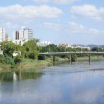 #Pracegover Foto: na imagem há o uma ponte, um rio, árvores e prédios