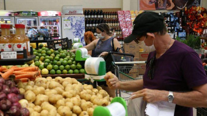 #Pracegover Foto: na imagem há pessoas escolhendo frutas e verduras em um supermercado