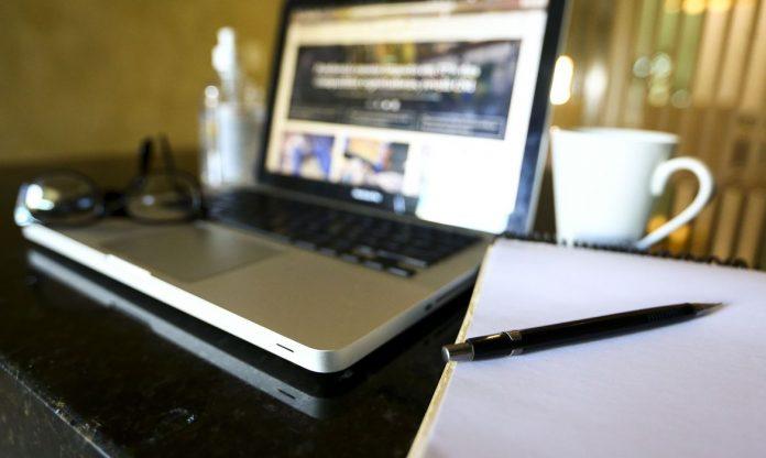 #Pracegover Foto: na imagem há um notebook, um óculos de grau, caneca, papel e caneta