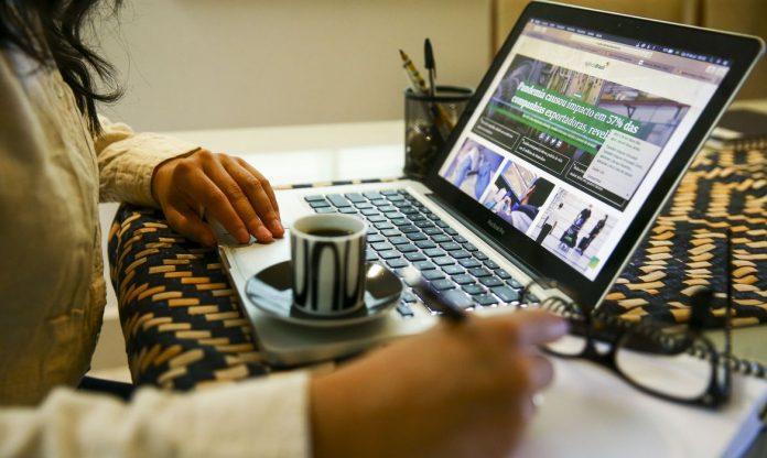 #Pracegover Foto: na imagem há duas mãos, uma xícara com pires, um óculos e notebook