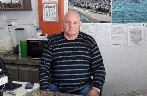 #Pracegover Foto: na imagem há um homem sentando com camisa listrada