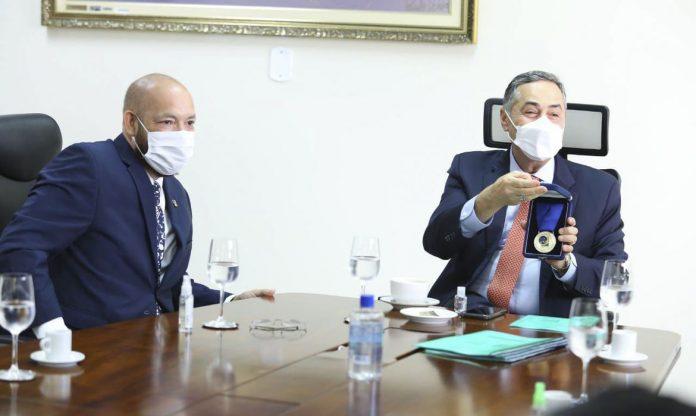 #Pracegover Foto: na imagem há dois homens, copos e garrafas de água, papéis, uma mesa e um dos homens segurando uma medalha