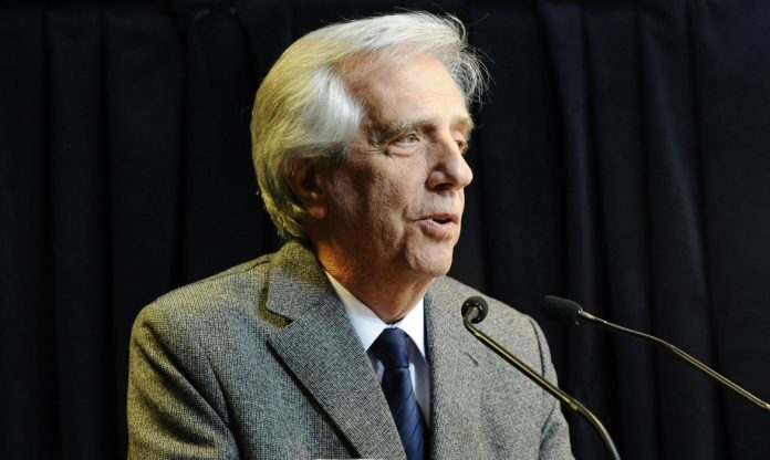 #Pracegover Foto: na imagem há um homem com cabelos grisalhos e de terno. Há também um microfone
