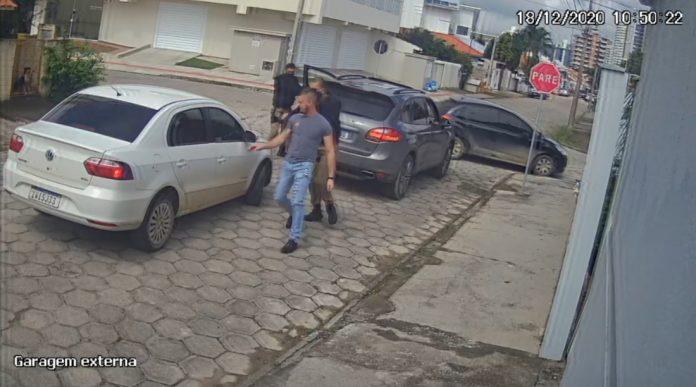 #Pracegover Foto: na imagem há três pessoas, carros e casas