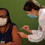 #Pracegover Foto: na imagem há duas mulheres. Uma delas está aplicando e a outra tomando a vacina