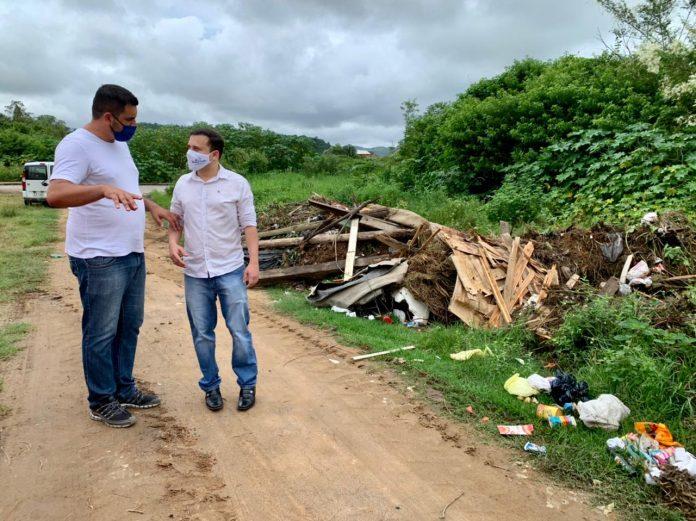 #Pracegover Foto: na imagem há dois homens, uma estrada, mato e entulhos