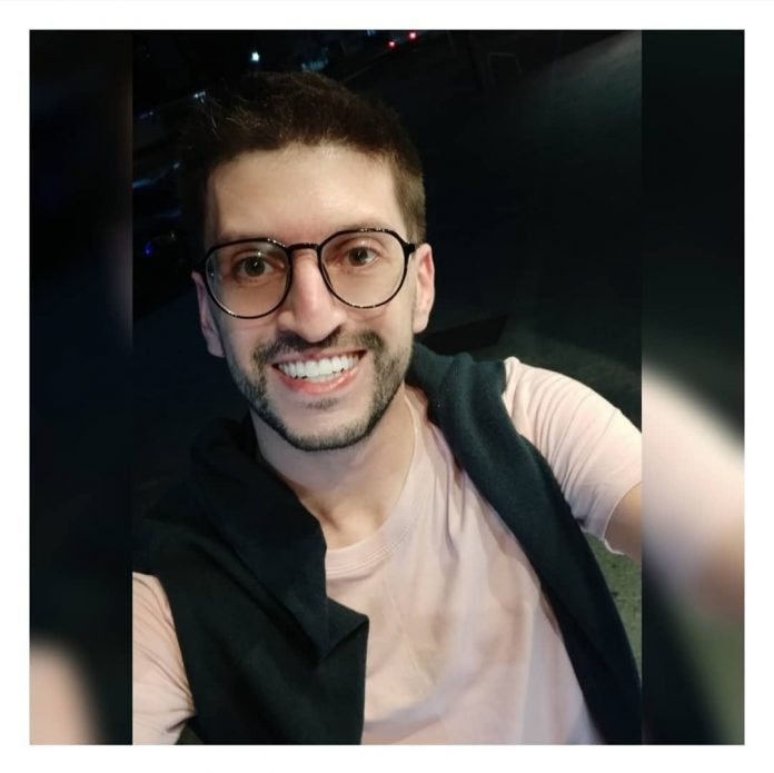 #Pracegover Foto: na imagem há um jovem sorridente, de óculos de grau, camiseta clara e também com um agasalho escuro nos ombros