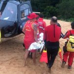 #Pracegover Na foto, Bombeiros resgatam o adolescente e o levam para o helicóptero
