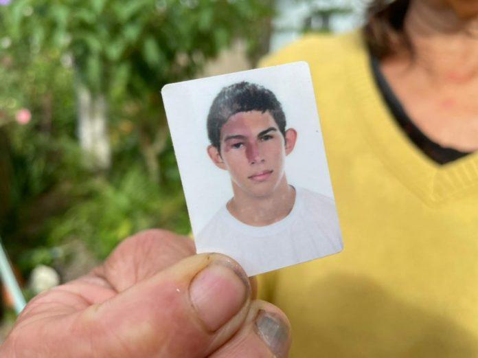 #Pracegover Foto: na imagem há uma mulher segurando um retrato 3/4 de um jovem
