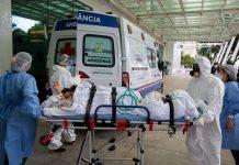 #Pracegover Na foto, um paciente sendo levado em uma maca por profissionais e ao fundo uma ambulância