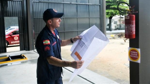 #Pracegover Na foto, a imagem de um bombeiro com um papel na mão