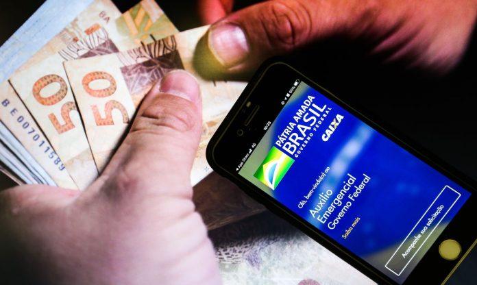 #Pracegover Foto: na imagem uma pessoa segura o celular. Há também algumas cédulas em real