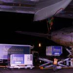 #Pracegover Foto: na imagem há caminhões, aeronave, pessoas e caixas