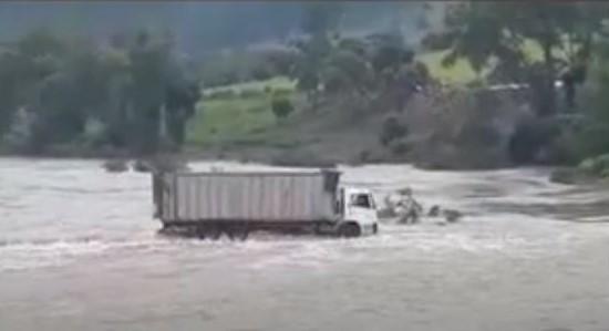 #Pracegover Na foto, aparece um caminhão atravessando uma ponte submersa
