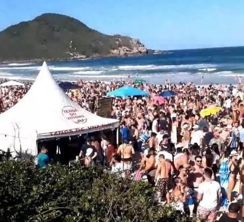 #Pracegover Na foto, pessoas em uma festa na Praia do Rosa durante a pandemia