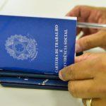 #Pracegover Foto: na imagem há carteiras de trabalho, mãos e caneta