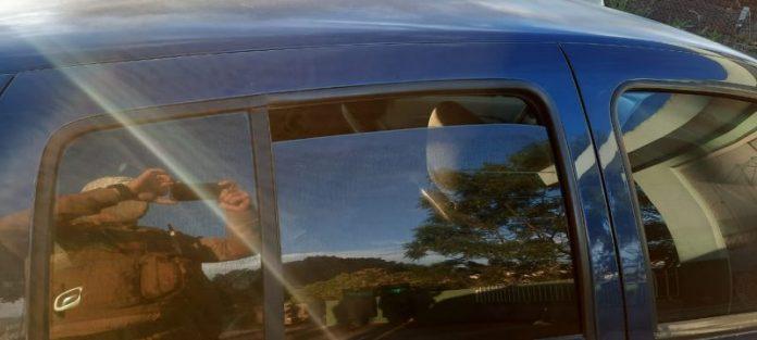 #Pracegover Na imagem, um policial fazendo uma foto da menina dentro do carro