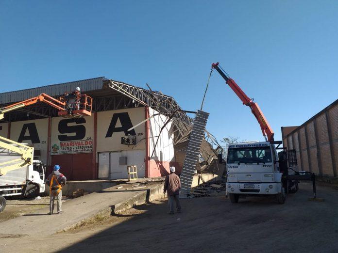 #Pracegover Foto: na imagem há uma construção com problemas no tehado, um caminhão e um homem