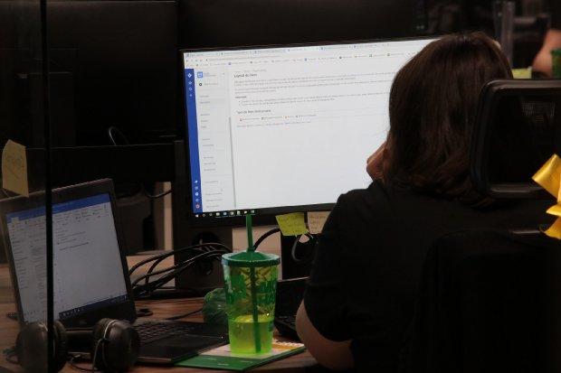 #Pracegover Foto: na imagem há uma mulher, um computador, notebook e materiais domésticos