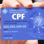 #Pracegover Foto: na imagem há um carão de CPF e uma mão