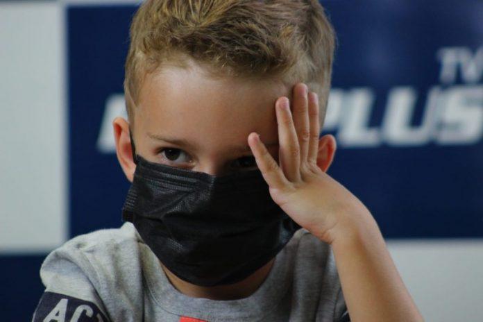#Pracegover Foto : na imagem há uma criança com uma mão na cabeça e de máscara
