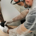 #Pracegover Na foto, um policial penal colocando tornozeleira eletrônica em um detento