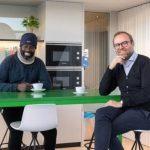 #Pracegover Foto: na imagem há dois home, uma mesa e cadeiras