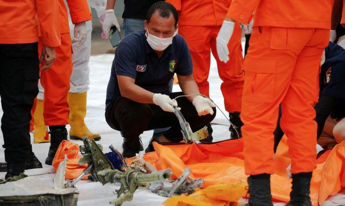 #Pracegover Na foto, autoridades inspecionam fuselagem do avião que caiu no mar