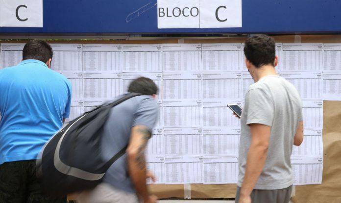 #Pracegover Foto: na imagem há três pessoas, conferindo uma lista. Uma delas está com um celular na mão e a outra com mochila nas costas