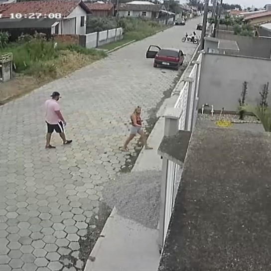 #Pracegover Na foto, um casal em frente a uma residência e mais a frente um veículo estacionado