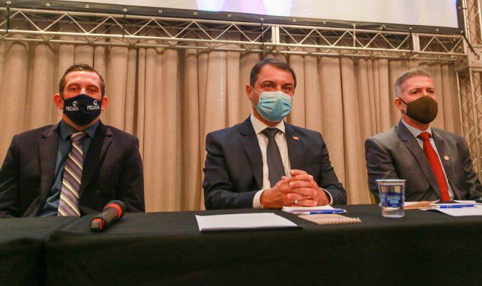 #Pracegover Foto: na imagem há três homens de máscara, há folhas e canetas