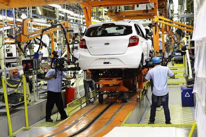 #Pracegover Na foto, trabalhadores durante montagem de carro em um fábrica