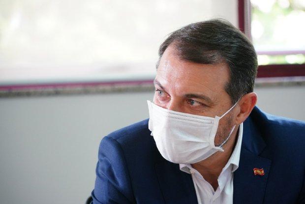 #Pracegover Foto: na imagem há um homem de terno azul, camisa branca e de máscara