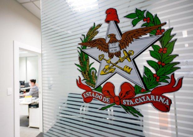 #Pracegover Na foto, o brasão de Santa Catarina colado em um vidro e ao fundo uma servidora trabalhando e usando máscara