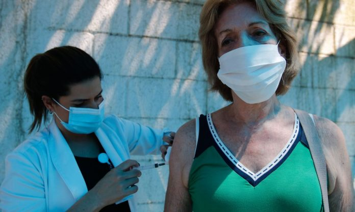 #Pracegover Na foto, uma profissional vacinando uma mulher, as duas usam máscara