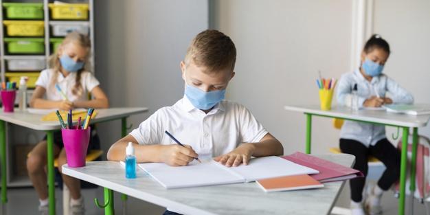 #Pracegover Na foto, crianças usando máscara, estão em sala de aula e mantendo distanciamento