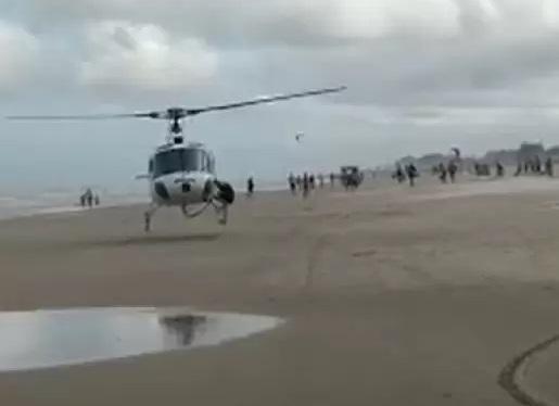 #Pracegover Foto: na imagem há um helecoptero, diversas pessoas, areia e água
