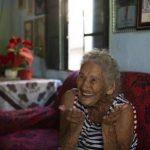 #Pracegover Foto: na imagem há uma idosa, sofa, uma mesa e janela