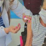 #Pracegover Foto: na imagem há uma muher jovem aplicando vacina em umda idosa que está de máscara