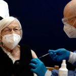 #Pracegover Foto: na imagem há três pessoas, uma delas é vacinada