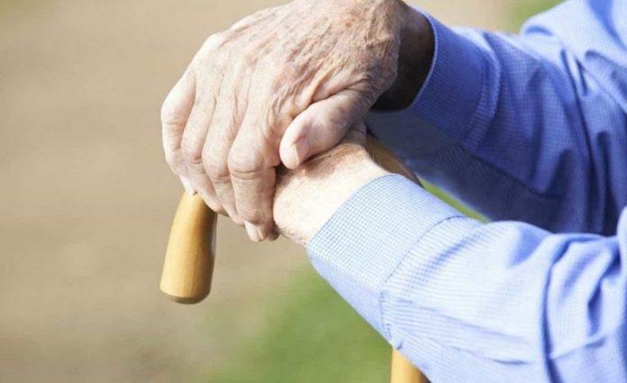 #Pracegover Foto: na imagem há as mãos de um idoso se apoiando em uma bengala. O homem está com roupa azul